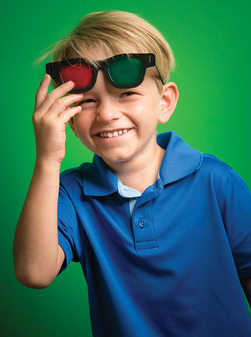 Photo of smiling young boy with red-green glasses