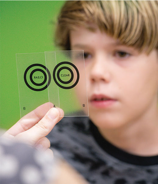 Photo of young patient looking at clear cards with circles on them