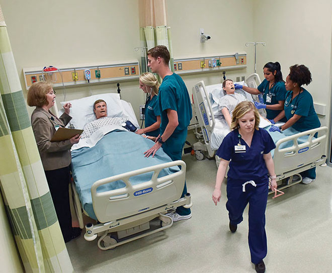 Photo of students working with simulated patients in mockup hospital room