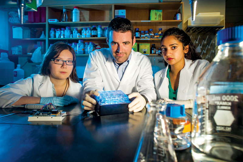 Photo of Guan-En Graham, Jeremy Day, and Jasmin Revanna in Day's lab