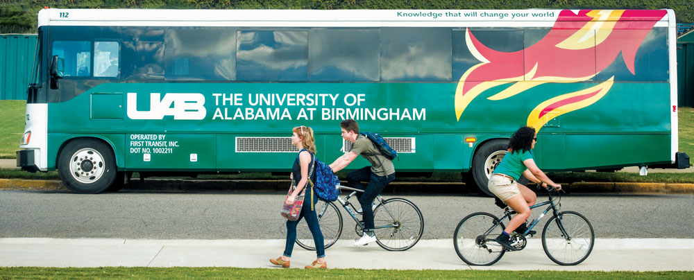 Photo of Blazer Express bus on road next to students on bicycles