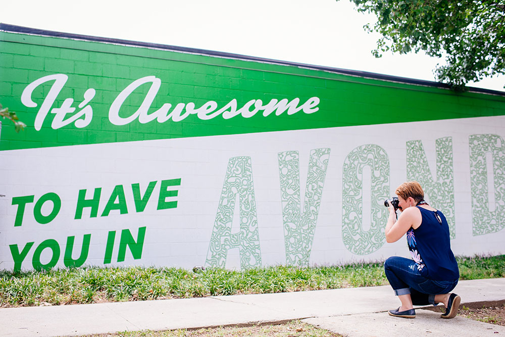 Photo of Viktoria Havasi taking picture of It's Nice to Have You in Avondale mural