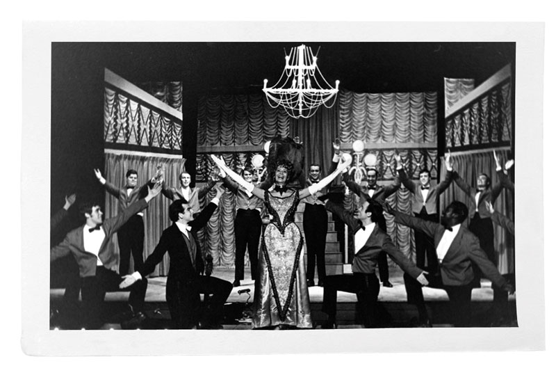 Black and white photo of performance of Hello Dolly!, with actress Boots Carroll at center stage