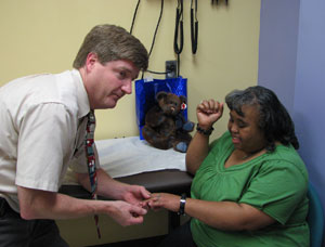 Dr Edward Lose visits with patient Ingrid Kidd