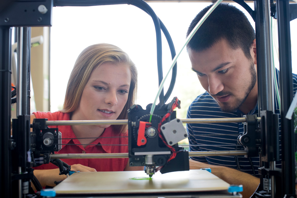 Severino and El-Husari looking at first prototype of their concept on a 3-D printer at the student-run UAB MakerSpace.