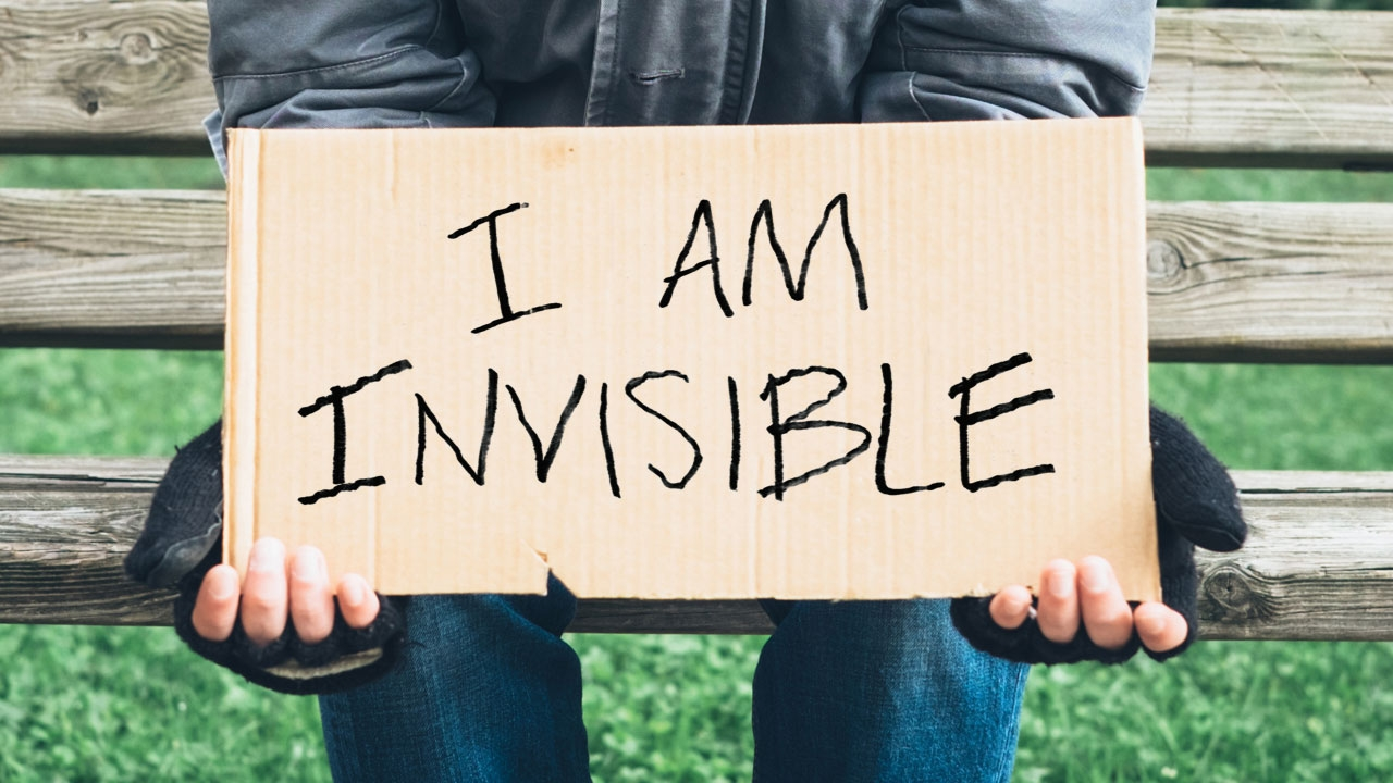Photo of man holding cardboard sign with headline: I Am Invisible