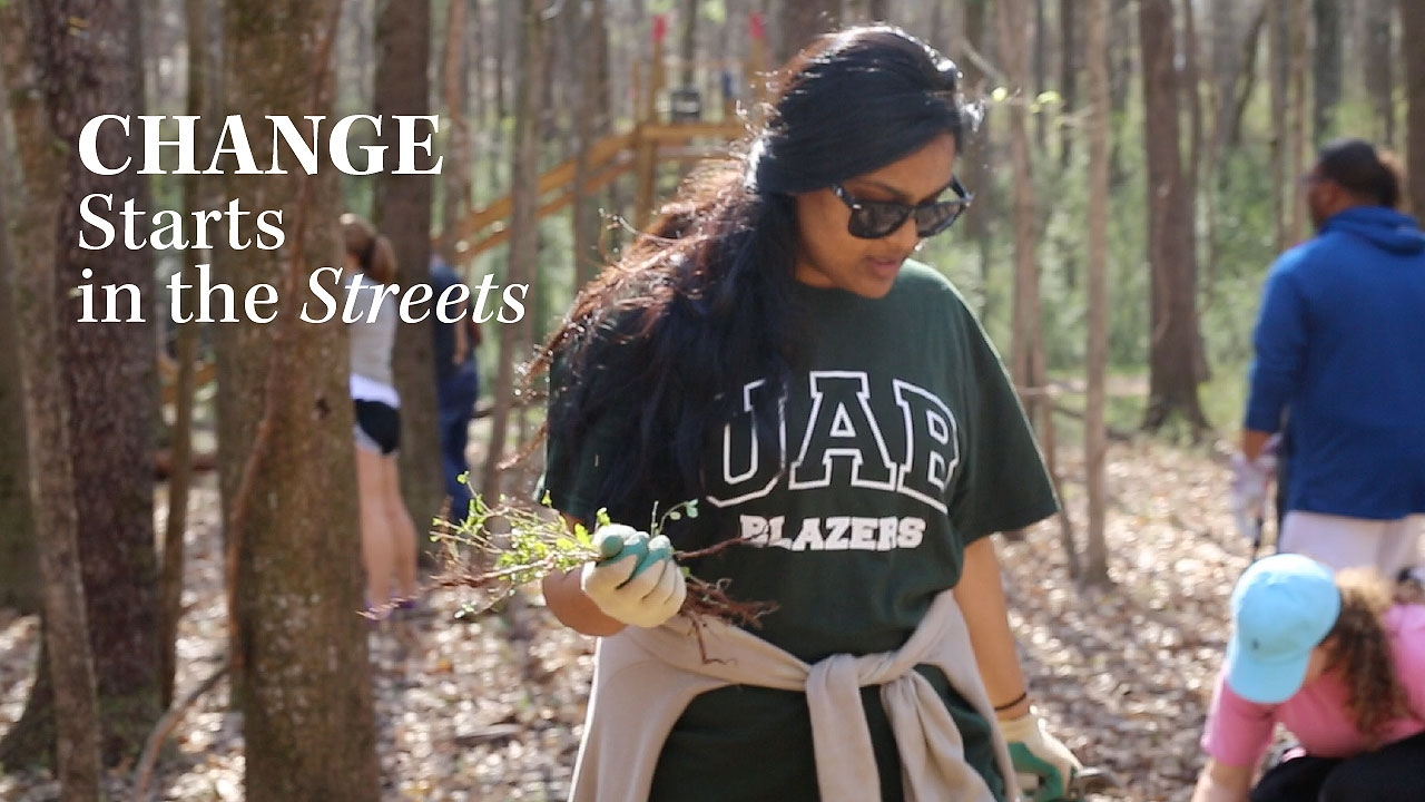 Photo of UAB student volunteering at Red Mountain Park; headline: Change Starts in the Streets