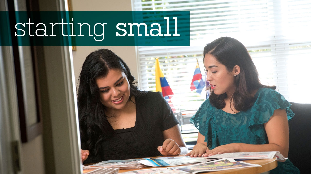 Photo of Dalila Gonzalez and Vanessa Vargas looking at Latino News newspapers; headline: Starting Small