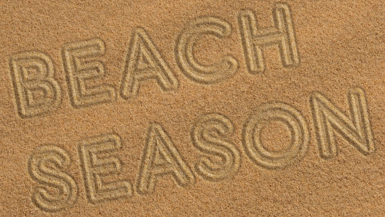 Photo illustration of sand with headline traced into it; headline: Beach Season