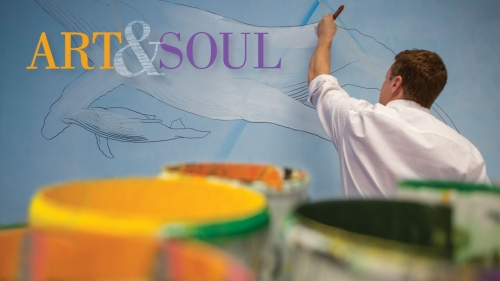 Photo of Adam Stermer painting a mural