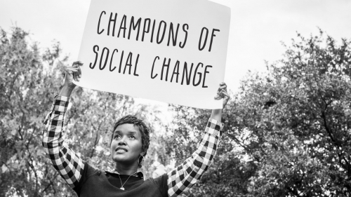 Photo of Ajanet Rountree holding up sign with headline: Champions of Social Change