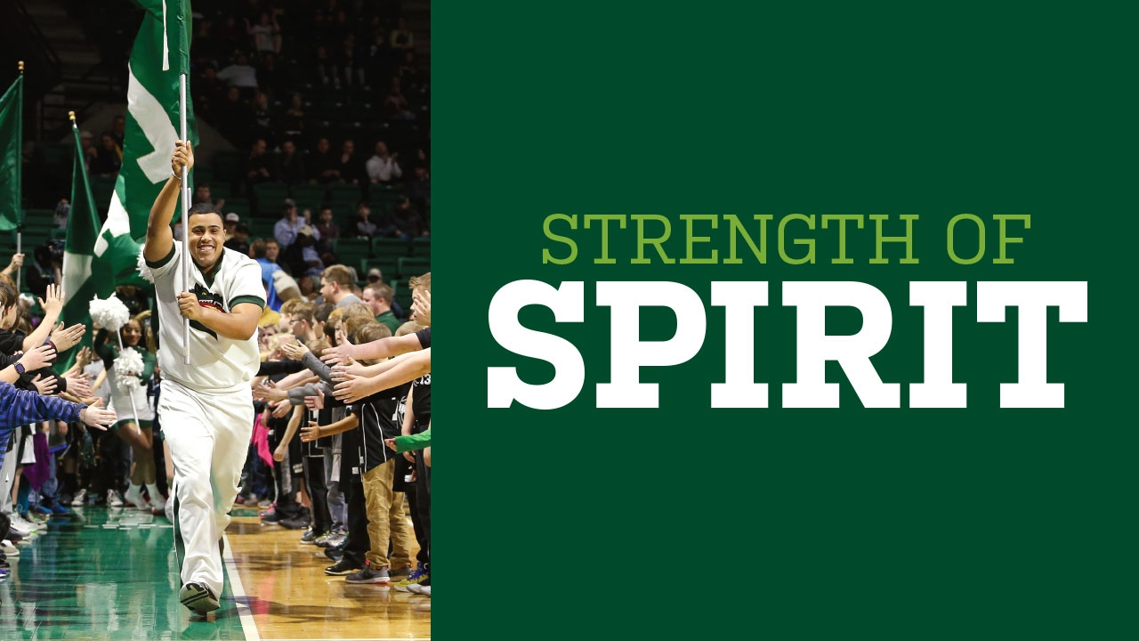 Photo of cheerleader Jamie Thrasher carrying UAB flag through Bartow Arena crowd; headline: Strength of Spirit