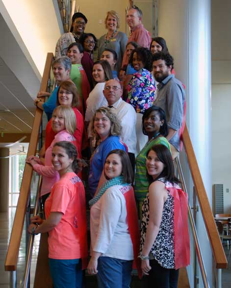 Group of 20 mentor teachers posing on stairwell in Heritage Hall.